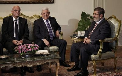 Palestinian Authority President Mahmoud Abbas, center, with Egyptian President Mohammed Morsi, right, at their first meeting in Cairo in July 2012. (photo credit: Maya Alleruzzo/AP)