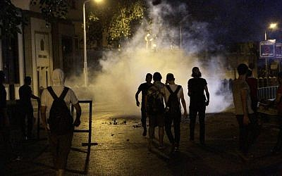Protesters walk through a cloud of tear gas during clashes with Egyptian riot police outside the Syrian embassy in Cairo on Wednesday, July 18, 2012. (photo credit: Ahmed Abdel-Fattah/AP)