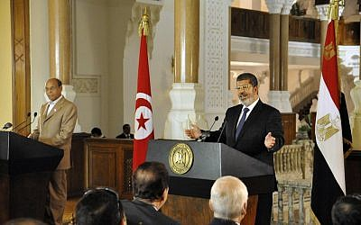 Tunisian President Moncef Marzouki, left, listens as Egyptian President Mohammed Morsi, right, speaks to reporters during a joint news conference at the Presidential palace in Cairo on Friday. (photo credit: AP/Egyptian Presidency)