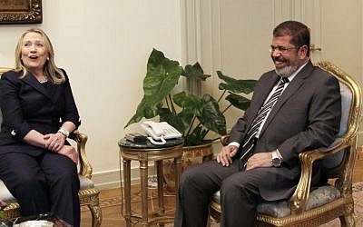 US Secretary of State Hillary Clinton and Egyptian President Mohammed Morsi share a laugh at the Presidential Palace in Cairo on Saturday. (photo credit: AP/Maya Alleruzzo)