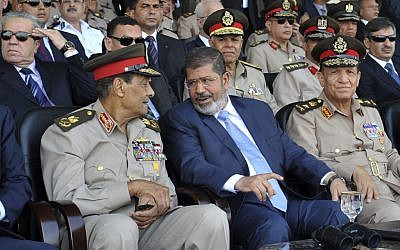 Mohammed Morsi (center) talks with Field Marshal Hussein Tantawi (photo credit:Sheriff Abd El Minoem, Egyptian Presidency/AP)