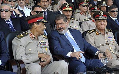 Mohammed Morsi (center) talks with Field Marshal Hussein Tantawi (photo credit:Sheriff Abd El Minoem, Egyptian Presidency/AP)