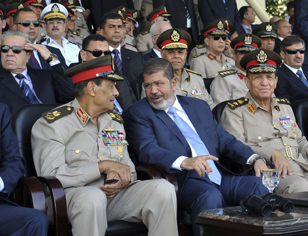 Mohammed Morsi (Center) talks with Field Marshal Hussein Tantawi (Left) (photo credit:Sheriff Abd El Minoem, Egyptian Presidency/AP)