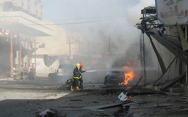 The body of a victim lies on the ground as firefighters try to extinguish flames after a car bomb attack in Kirkuk, Iraq in June 2012. (Photo credit: AP /Emad Matti, File)
