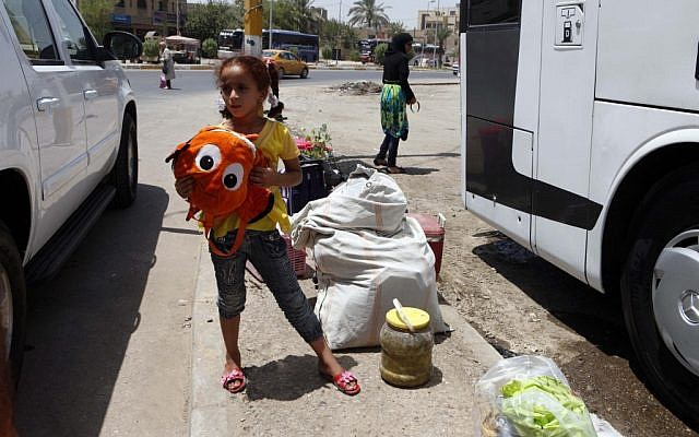 Layla Fadhil, an Iraqi refugee, stands with her family's belongings after her arrival from Syria in the Mansour neighborhood of Baghdad on Friday. (photo credit: AP/Karim Kadim)