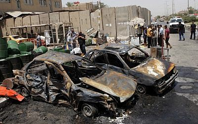 People inspect the aftermath of a car bomb attack in Baghdad on Monday. (photo credit: AP /Karim Kadim)