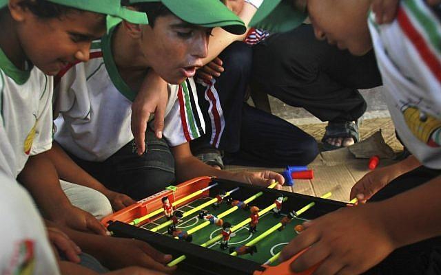 Palestinian boys play table football at a summer camp run by Hamas inside a school in Al-Qarara near Khan Younis, southern Gaza Strip, on Wednesday, July 11, 2012. (photo credit: Adel Hana/AP)