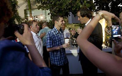 Gilad Shalit, center, mingles and speaks to the French Ambassador to Israel Christophe Bigot, in Tel Aviv Thursday. (photo credit: Ariel Schalit/AP)