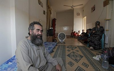 Abo Manar Ahmed Abazeed, 48, and his family from Tal Shehab city in Syria, are seen in their temporary home in Irbid, Jordan on Tuesday (photo credit: AP/Mohammad Hannon)