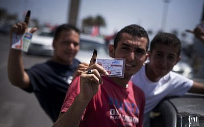 Libyan men hold their elections ID cards while celebrating election day in Tripoli on July 7, 2012. (photo credit: Manu Brabo/AP)