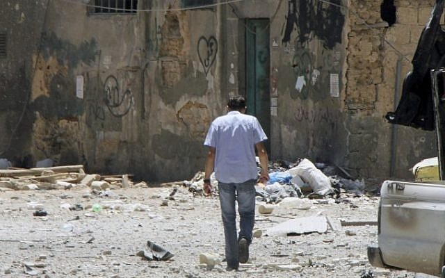 A man walks along a shattered street in Damascus on Friday (photo credit: AP/Bassem Tellawi)