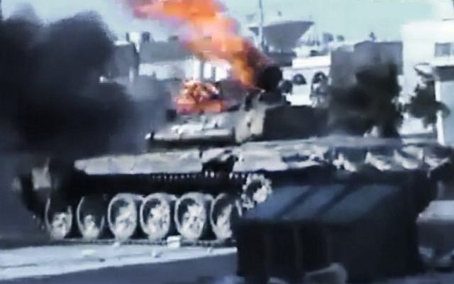 This image taken from an amateur video shows a Syrian military tank on fire during clashes with Syrian government troops in Aleppo on Monday. (photo credit: Ugarit News/AP video)