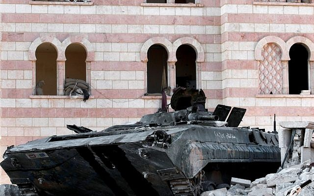 A damaged Syrian military tank is seen in the border town of Azaz, some 20 miles (32 kilometers) north of Aleppo, Syria, on Tuesday (photo credit: AP/Turkpix)