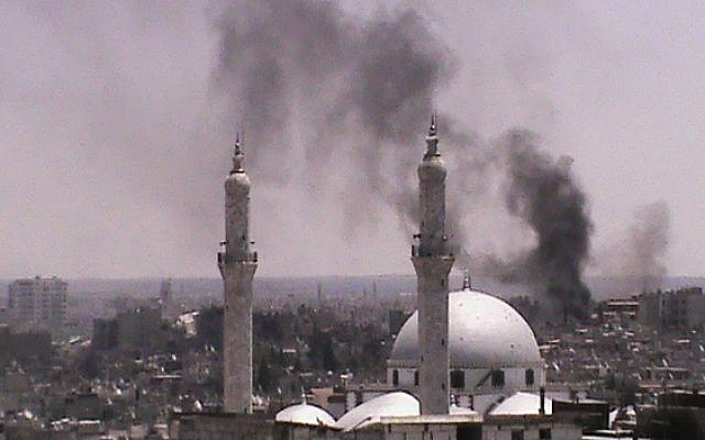 Black smoke rises from buildings near a mosque from purported forces shelling in Homs, Syria on July 11, 2012. (photo credit: Shaam News Network/AP)
