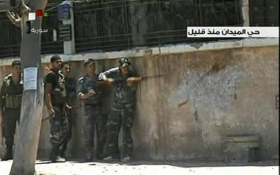 Syrian troops clash with rebels in Damascus' Midan neighborhood in July 2012. (AP Photo/SANA via AP video)