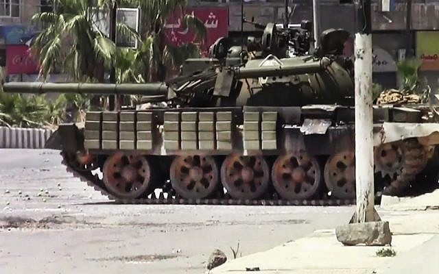 This image made from amateur video released by the Shaam News Network and accessed Sunday, shows a Syrian military tank in Daraa, Syria. (Photo credit: AP/Shaam News Network)