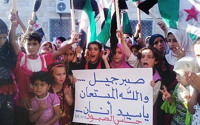 "Syrian children chanting slogans hold a poster with Arabic that reads, ""Patience is good, and God is the one who helps,"" in Idlib province, Syria, on Wednesday. (photo credit: AP Photo/Shaam News Network, SNN)"