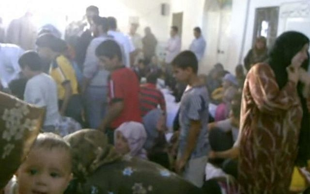 This image made from amateur video accessed by AP on Friday purports to show families gathered around bodies of victims killed by violence that, according to anti-regime activists, was carried out by government forces in Tremseh, Syria. (photo credit: AP/Hama Revolution 2011)