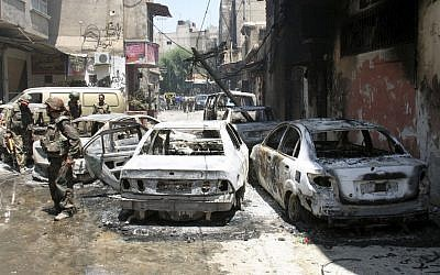 Syrian soldiers stand next to burned cars after they regained control of the district of Midan, in the southern part of Damascus, Syria, Friday, July 20, 2012. (photo credit: Bassem Tellawi/AP)