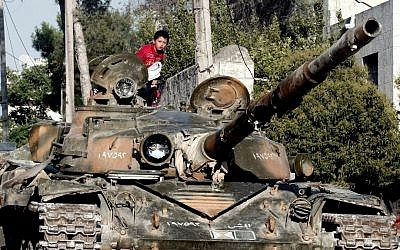 A Syrian boy sits atop a damaged military tank at the border town of Azaz, some 20 miles (32 kilometers) north of Aleppo last month (photo credit: AP/Turkpix)