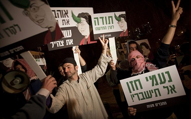Right-wing activists dressed as Arabs demonstrate against the New Israel Fund in January 2010. The signs show the NIF's former president Naomi Chazan with a horn sprouting from her head and accuse the fund of financing organizations that contributed to the Goldstone report (photo credit: AP/Dan Balilty)
