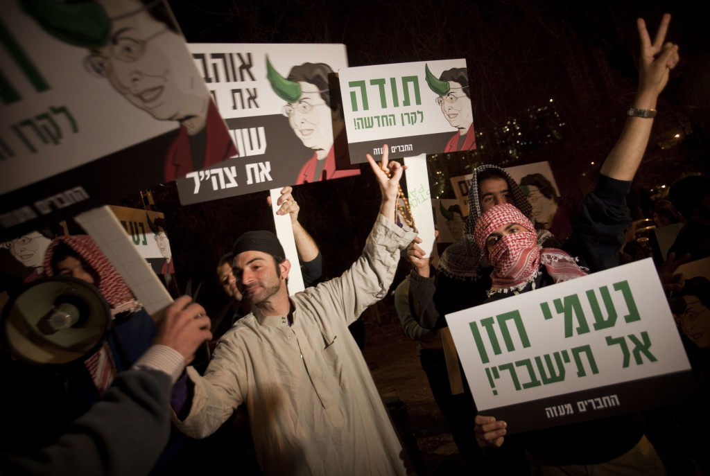 Right-wing activists dressed as Arabs demonstrate against the New Israel Fund in January 2010. The signs show the NIF's president Naomi Chazan with a horn sprouting from her head and accuse the fund of financing organizations that contributed to the Goldstone report (photo credit: AP/Dan Balilty)