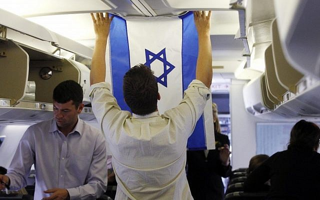 Aide Charlie Pearce examines an Israeli flag on the charter plane of Republican presidential candidate and former Massachusetts Gov. Mitt Romney before he boards at London Stansted Airport, Saturday. (photo credit: AP)