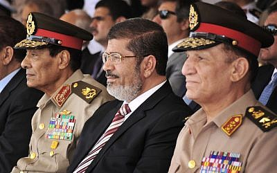 Egyptian President Mohammed Morsi flanked by high-ranking generals (photo credit: AP/Mohammed Abd El Moaty)