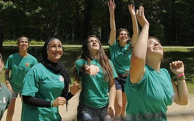 Jordanian, Egyptian, and Israeli girls work and play together as a team during a game of volleyball at the Seeds of Peace summer camp in Otisfield, Maine. (photo credit: Robert F. Bukaty/AP)