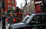 A woman waits at a traffic light in one of London's busiest streets. (Photo credit: Gili Yaari/Flash90)