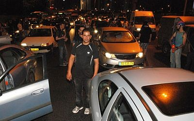Protesters carry signs as they block traffic on Tel Aviv's Ayalon freeway Sunday night (photo credit: Artiom Degel)