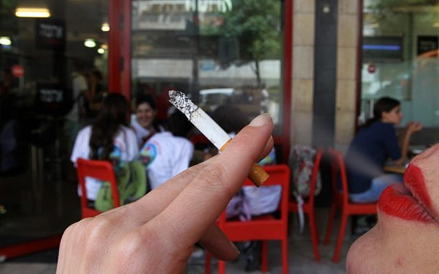 Illustrative photo of a woman smoking a cigarette outside an Israeli cafe. (Nati Shohat/Flash90)