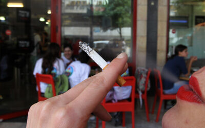 A woman smokes a cigarette outside a cafe. Israel took another step towards becoming smoke-free when strict regulations came into effect that limit smoking in public places. (photo credit: Nati Shohat/Flash90)