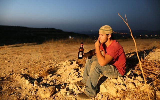 Smoking a cigarette and drinking beer on  the outskirts of the Havat Gilad settlement. Finance Minister Yuval Steinitz raised beer and cigarette prices overnight on July 25. (photo credit: Nati Shohat/Flash90)