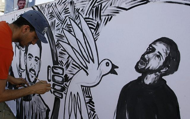 Palestinian painters paint murals of Mahmoud Sarsak (R) and other prisoners, in the southern Gaza Strip on June 10, 2012. Sarsak, a former member of the Palestinian National Soccer Team, was released after three-month hunger strike. (photo credit: Abed Rahim Khatib/Flash 90)