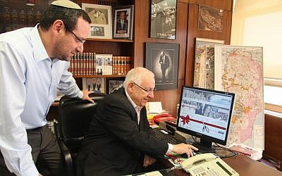 Knesset Speaker Reuven Rivlin (seated) cuts a 'virtual red ribbon' inaugurating the Knesset's updated website (photo credit: Knesset spokesperson)