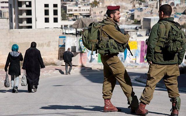 Israeli soldiers patrol among Palestinian pedestrians in Hebron