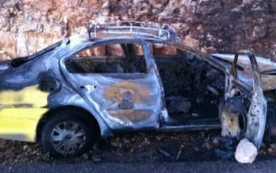 A burnt-out Palestinian taxi in the wake of a firebombing attack near the settlement of Bat Ayin (photo credit: Israel Police)
