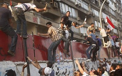 Egyptian protesters demolish a concrete wall protecting the Israeli embassy in Cairo, September 9, 2011. ( AP/Amr Nabil)