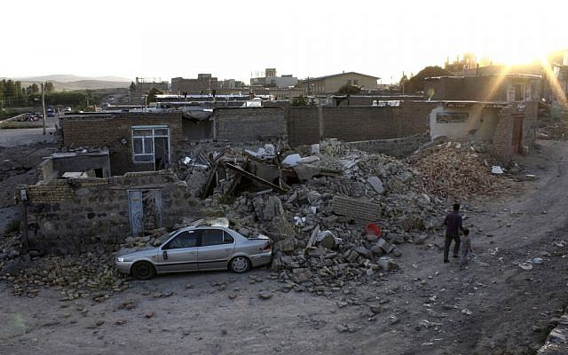Ruins of a houses are seen after an earthquake in the city of Varzaqan in northwestern Iran, on Saturday. (photo credit: AP/Mehr News Agency, Hamed Nazari)