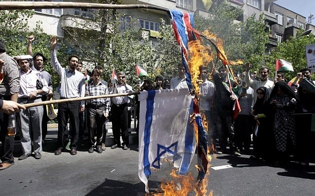 Iranian demonstrators burn an Israeli and British flag during a rally marking Quds Day, on the last Friday of Ramadan, in Tehran last year. (photo credit: AP/Vahid Salemi)