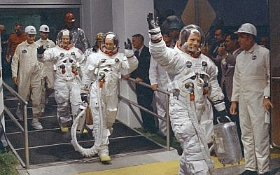"""In this July 16, 1969 file photo, Neil Armstrong waving in front, heads for the van that will take the crew to the rocket for launch to the moon at Kennedy Space Center in Merritt Island, Florida. Armstrong commanded the Apollo 11 spacecraft that landed on the moon July 20, 1969. He radioed back to Earth the historic news of """"one giant leap for mankind."""" Armstrong and fellow astronaut Edwin """"Buzz"""" Aldrin spent nearly three hours walking on the moon, collecting samples, conducting experiments and taking photographs. (photo credit: AP Photo/NASA)"""