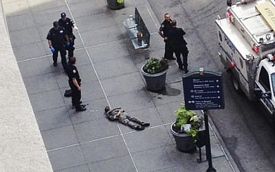 New York City police approach the lifeless body of Jeffrey Johnson lying on a sidewalk near the Empire State Building in New York following a shooting on Friday, August 24. (photo credit: AP/Guillermo Ratzlaff)