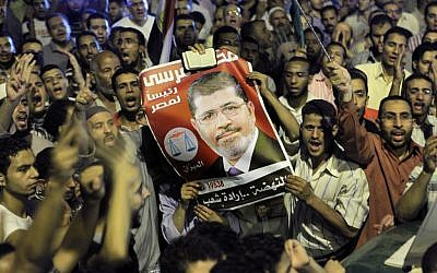 Thousands of supporters raise a poster of Egypt's Islamist President Mohammed Morsi as they celebrate in Tahrir Square in Cairo, late Sunday, Aug. 12, 2012. (photo credit: Amr Nabil/AP)