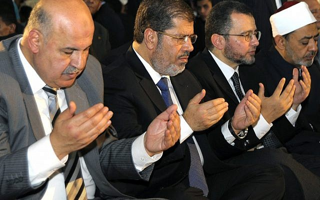 Egyptian President Mohammed Morsi prays alongside members of his cabinet during the festival of Eid Al-Fitr (photo credit: AP/Egyptian Presidency)