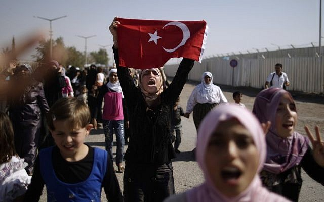 Syrian women and girls shout slogans on Tuesday as they march toward the border, pleading for entry into neighboring Turkey (photo credit: AP/Muhammed Muheisen)