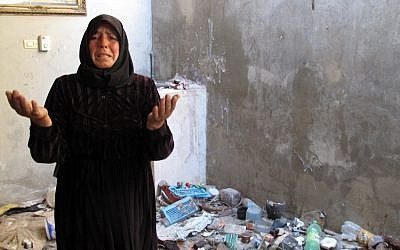 Fatoum Obeid, 50, stands in a pile of trash left by Syrian soldiers who occupied her home in Atarib, Syria. In recent months rebels have seized a huge swath of territory in northern Syria, giving them a freedom to move and organize unprecedented in the 17-month conflict. (photo credit: AP/Ben Hubbard)