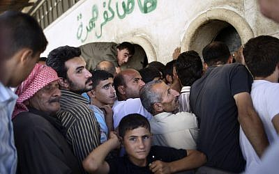 Syrians wait in line to buy bread in the outskirts of Aleppo, Syria (photo credit: Muhammed Muheisen/AP)