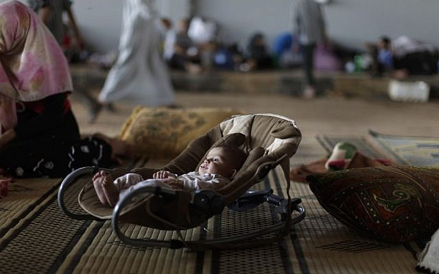 A Syrian child lies in a safety seat while his family takes refuge at the Bab Al-Salameh border crossing, in hopes of entering one of the refugee camps in Turkey. (file photo credit: AP/Muhammed Muheisen)