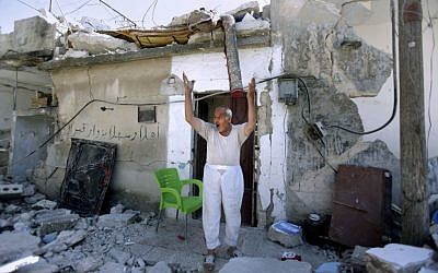 A Syrian man standing in front of his house, which was destroyed by Syrian government forces shelling in Azaz, on the outskirts of Aleppo, August 28, 2012 (photo credit: AP/Muhammed Muheisen)